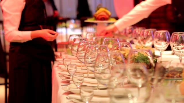 Obers zetten glazen neer op een diner tafel